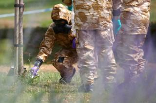 People in hazardous material protective suits collect an item in Queen Elizabeth Gardens in Salisbury, Britain