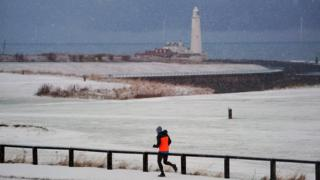 "A jogger runs past St Mary""s Lighthouse in Whitley Bay on the Northumberland coast."