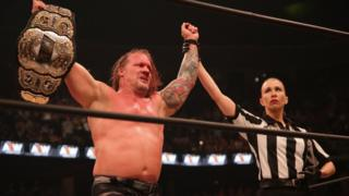 Chris Jericho holding up the AEW championship in a wrestling ring after his match