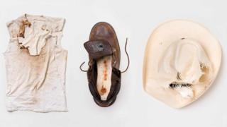 Хаиме Сантананын шляпасы жана футболкасы. Жастин Годжердин бут кийими.