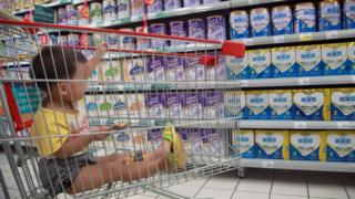 A baby stays in a shopping cart as his mother selects baby milk in a supermarket in Haikou, south China's Hainan province