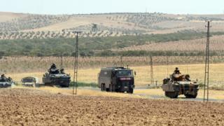Turkish military vehicles return from the Syrian border