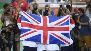 British Gold medallists hold up a flag as they pose on the podium after the women's Team Pursuit finals track cycling event at the Velodrome during the Rio 2016 Olympic Games