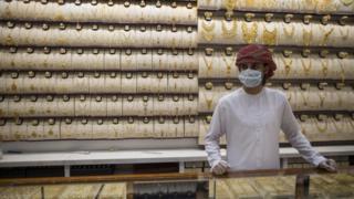 A seller wears a protective mask in a gold shop at Dubai Gold Market, Dubai