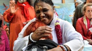 Indian spiritual leader Mata Amritanandamayi (C), popularly know as 'Amma' (The Mother) or also as 'The Hugging Saint,' hugs a woman during a followers's gathering on October 26, 2016 in Paris