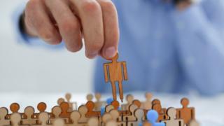 Mão levanta um boneco de papel de grupo com dezenas de figuras semalhantes