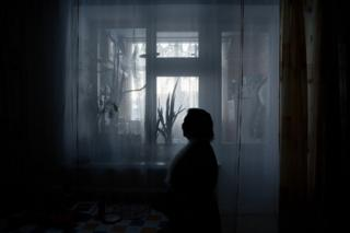 Liliya Yamkina (Born. 1944) looking through the window in her apartment. Yar-Sale village, Yamal Peninsula, Siberia, Russia.
