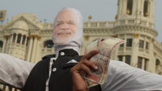 A man holds up 1000 rupee notes against a prop of Modi