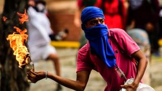 An opposition demonstrator prepares to throw a molotov cocktail during clashes with riot police in an anti-government protest in Caracas