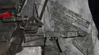 The drawing on the base of the statue (on the right) which shows Germany's StG 44 rifle