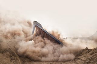 Падающее здание в облаке пыли