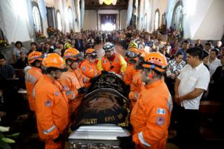 Rescuers carry the coffin of Juan Fernando Galind