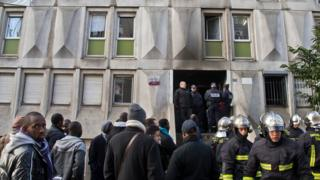 Firefighters and migrants outside a migrant reception centre in Boulogne-Billancourt, west of Paris, on 16 December 2016 after a fire broke out