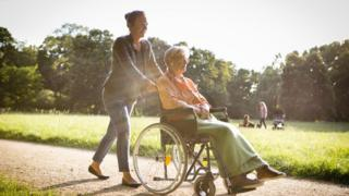 A young woman pushes an older woman in a wheelchair