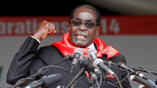 Robert Mugabe raises a fist while delivering a speech from a podium