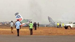 Des débris de l'appareil à l'aéroport de Wau où plusieurs personnes s'activent pour retrouver des survivants