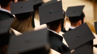 Students in graduate hats at a graduation.