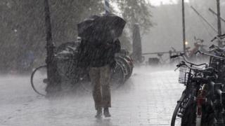 A man holds an umbrella is windy and wet conditions