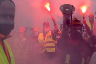 People in fluorescent jackets hold burning flares