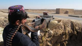 An Afghan Local Police (ALP) personnel keeps watch during an ongoing battle with Taliban militants in the Marjah district of Helmand Province on December 23