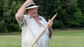 Gerard Depardieu rests during hand-scything