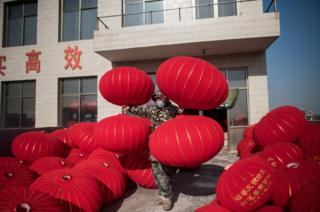 A Chinese worker places red lanterns on a rooftop in order to let them dry out.
