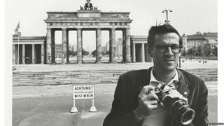 Flip Schulke in front of the Brandenburg Gate in West Germany, early 1960s
