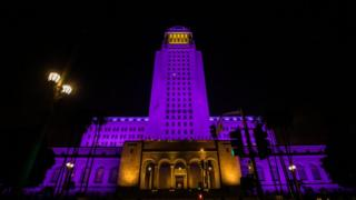 city_hall_building_lit_up_in_purple_and_yellow