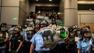 Cảnh sát Hong Kong đứng canh gác bên ngoài một đồn cảnh sát hôm 17/8