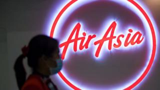 Woman wearing a face mask walks past the logo of AirAsia at Don Mueang Airport in Bangkok, Thailand.