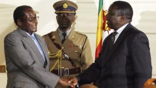 Robert Mugabe and Morgan Tsvangirai shake hands