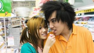 Casal de jovens japoneses; moça dá uma comida na boca do namorado