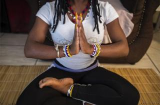 A woman sitting on the ground holds a yoga pose, with her legs crossed and he hands clasped together.