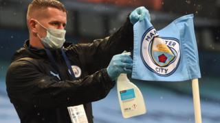 A member of staff disinfects the corner flag at Manchester City
