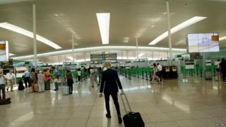 A passenger heads to security at Barcelona's El Prat airport