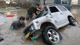 Residents try to upright a vehicle stuck in a flood hit area in Kurashiki