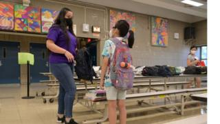 Teacher at an elementary school hands a graduation gift to a pupil at the end of the school year