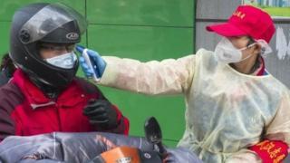 武汉市社区工作人员为进小区者量体温