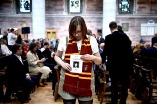 in_pictures A friend of Lyra McKee holds an order of service as she attends the funeral of murdered journalist Lyra McKee