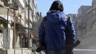 Молодой сирийский журналист с фотоаппаратом и автоматом для самообороны