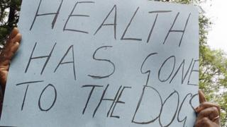 A protester holds up a poster that reads 'Health has gone to the dogs'
