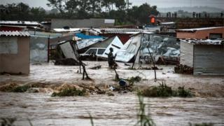 A Mamelodi resident wades through water in an area where 700 shacks were reportedly destroyed during heavy rains, Pretoria, South Africa, 09 December 2019