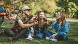 Grupo de amigos en un parque tomando cerveza con cervezas detrás.