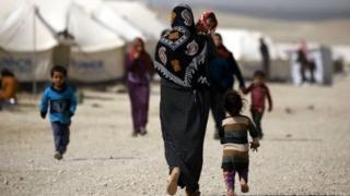 سيدة تحمل طفلا في أحد مخيمات اللاجئين قرب الحدود السورية العراقية