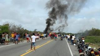 People watch as smoke billows from an overturned tanker truck that caught fire near Pueblo Viejo, Colombia, 6 July