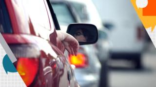 view of back of car, women's face in wing mirror as she looks at the queue of traffic ahead