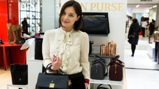 سيدة تحمل حقيبة يد في متجر للحقائب والسلع النسائية