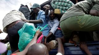Several men climbing onto the back of a packed lorry with their belongings after being released from a prison in in Bujumbura, Burundi.
