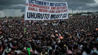 "Supporters of Kenya""s opposition National Super Alliance (NASA) coalition hold a banner during a political rally in Kisumu, western Kenya, on October 20, 2017."