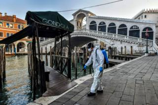 in_pictures A municipal company employee sprays disinfectant in public areas at the Rialto Bridge in Venice. 11 March 2020.